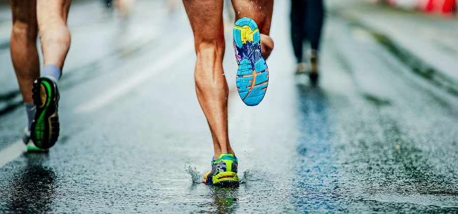 A group of runners legs and feet hitting a rainy roadway